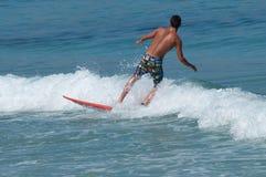 Занимаясь серфингом серфер плавая на волну Стоковое Изображение RF