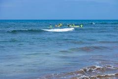 Занимаясь серфингом урок в Maspalomas: группа в составе учащийся surfboard с инструкторами в море Maspalomas, Испания - 18-ое июл стоковые фотографии rf