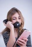 Занятая девушка говоря на телефоне и на smartphone Стоковое Фото