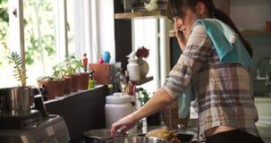 Занятая женщина в кухне варя еду и говоря на телефоне сток-видео