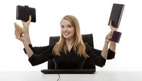 Занятая женщина на ее столе стоковая фотография