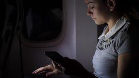 Занятая женщина со смартфоном в самолете сидя около окна, ночного полета видеоматериал