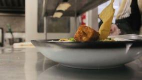 Занятая команда шеф-поваров и кельнеров и кухня комплектуют штаты подготавливая и служа еда в коммерчески кухне сток-видео