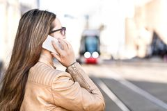 Занятая коммерсантка имея телефонный звонок пока ждущ трамвай стоковое фото rf