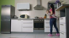 Занятая мать варя в кухне держа сына младенца сток-видео