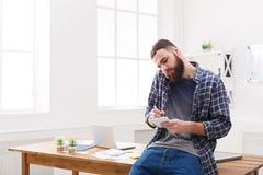 Занятая молодая беседа бизнесмена на телефоне в офисе Стоковые Фотографии RF