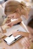 Занятая молодая женщина на офисе есть и используя таблетку Стоковые Фото