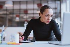 Занятая молодая женщина работая на ее столе Стоковая Фотография