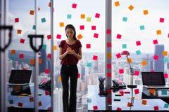 Занятая персона писать много липких примечаний на большом окне Стоковая Фотография