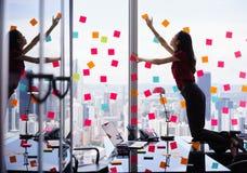 Занятая персона прикрепляя много липких примечаний на большом окне Стоковая Фотография