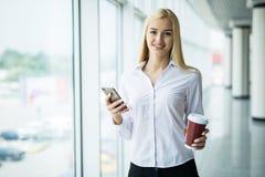 Занятая польза коммерсантки телефон с чашкой кофе в другом рука около большого панорамного окна в офисе Стоковые Фото