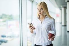 Занятая польза коммерсантки телефон с чашкой кофе в другом рука около большого панорамного окна в офисе Стоковые Изображения RF
