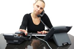 Занятая секретарша в офисе с 2 телефонами стоковое фото