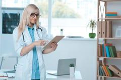 Занятие доктора молодой женщины в офисе больницы Стоковое фото RF
