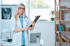 Занятие доктора молодой женщины в офисе больницы Стоковые Фото