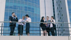 Занятые бизнесмены outdoors на террасе офисного здания сток-видео