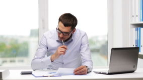 Занятый бизнесмен с компьтер-книжкой и бумагами в офисе видеоматериал