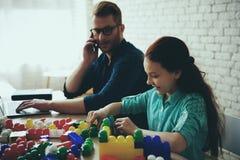 Занятый одиночный отец работает и выглядит как дочь стоковое изображение