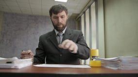 Занятый работник офиса штемпелюя входящие документы документы scatter бизнесмена вокруг акции видеоматериалы