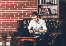 Занятый человек вызывает телефонный номер Бизнесмен в его шкафе за его ноутбуком на предпосылке стены с декоративными кирпичами стоковые изображения