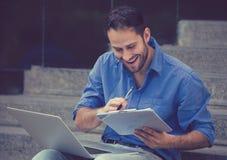 Занятый человек работая на компьтер-книжке вне корпоративного офиса Стоковые Изображения