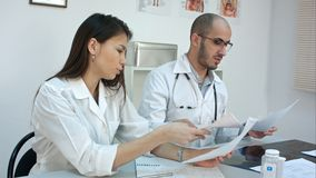 2 занятых доктора работая с бумагами и изображениями рентгеновского снимка, отвечая телефонными звонками, предписывая пилюльками  Стоковая Фотография RF