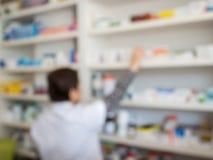 запачкайте аптекаря принимая медицину от полки в фармации Стоковое Изображение