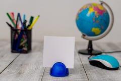 Запачкайте изображение канцелярских принадлежностей плюс искусственный глобус на деревянном столе Стол пиломатериала полный с зап стоковая фотография