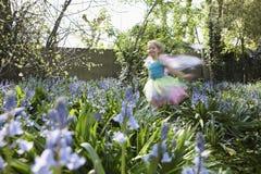 Запачканная девушка в Fairy костюме бежать в цветочном саде стоковые изображения