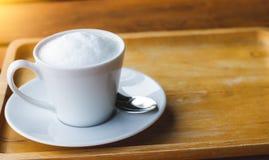 Запачканная кружка белого кофе фото с пеной молока на деревянном подносе на деревянном столе Космос для входного сигнала текста Стоковая Фотография