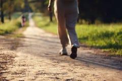 Запачканная предпосылка с девушкой в светлых одеждах которая идет через парк стоковая фотография
