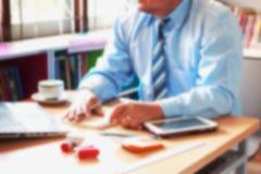 Запачканная предпосылка офиса, работа под рукой работника офиса Стоковое фото RF