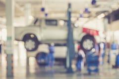 Запачканная предпосылка: Тайские люди ремонтируя автомобиль в гараже стоковые фото