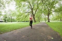 Запачканное движение женщины jogging в парке Стоковые Изображения RF