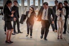 Запачканное движение напористых бизнес-леди и бизнесмена Стоковые Фото