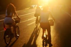 Запачканное фото велосипедистов на заходе солнца Стоковые Изображения RF