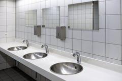 Запачканные белые washbasins и сияющие faucets в туалете с пирофакелом Стоковые Фото