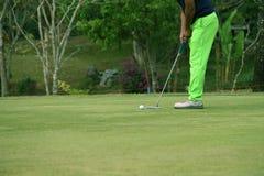 Запачканные игроки в гольф patting гольф в поле для гольфа вечера в t стоковое изображение rf