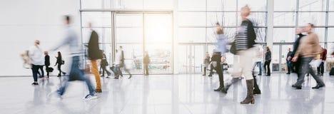 Запачканные люди коммутируя путешествующ идти в современную залу стоковая фотография