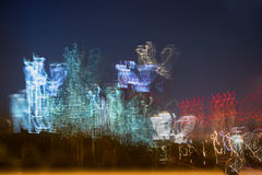 Запачканные небоскребы против синего неба Многоэтажные здания на ноче, загоренные окна Современный город на автомобиле Стоковое Фото