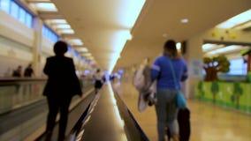 Запачканные люди двигая дальше плоский эскалатор внутри крупного аэропорта сток-видео