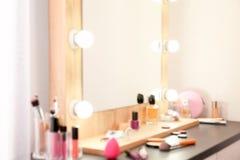 Запачканный взгляд таблицы с продуктами макияжа и зеркала около белой стены, крупного плана стоковая фотография rf