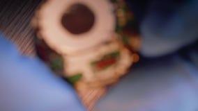 Запачканный взгляд часов стороны Руки в голубых перчатках повернуть его сверх и положить на таблицу акции видеоматериалы