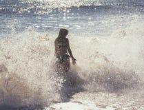 Запачканный силуэт девушки в брызге пены моря и слепимости солнечного света Стоковые Изображения