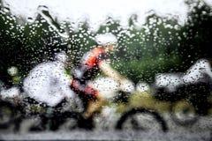 Запачканный силуэт за стеклом воды падений всадника на велосипеде Стоковое Изображение RF