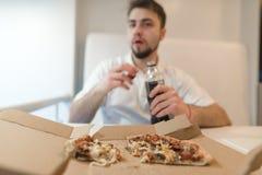 Запачканный человек с питьем в его руках против коробки пиццы Человек ест fasfood и выпивает колу Стоковая Фотография RF