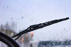 Запачкано грязное лобовое стекло автомобиля с включенным стеклянным уборщиком, в больших фронте города и задней части предпосылки стоковые изображения