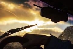 Запачкано грязное лобовое стекло автомобиля с включенным стеклянным уборщиком, в больших фронте города и задней части предпосылки стоковое фото