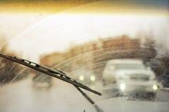Запачкано грязное лобовое стекло автомобиля с включенным стеклянным уборщиком, в больших фронте города и задней части предпосылки стоковые фото