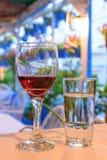 Запачкан бокал с красным вином и стеклом воды на таблице, предпосылка Стоковое Фото
